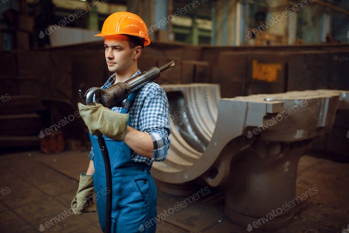 Male worker holds pneumatic jackhammer on factory