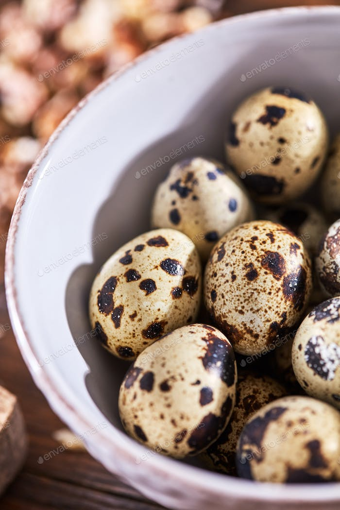 Closeup of organic quail eggs in a white plate on a wooden table. Healthy food. Top view