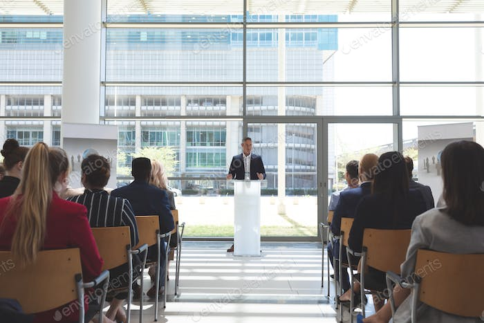 Front view of male mixed race businessman speaks in a business seminar in office building