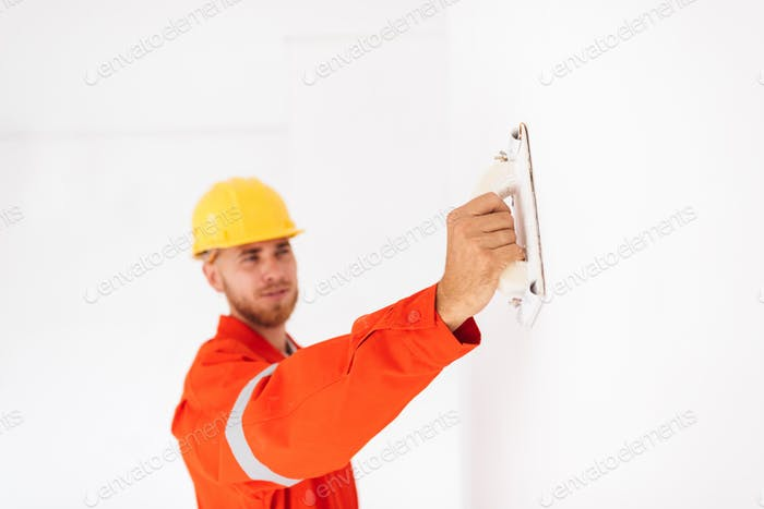 Close up foreman in orange work clothes and yellow hardhat using