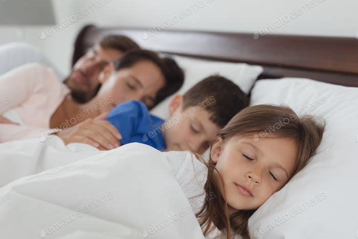 Front view of Caucasian family sleeping together in bed in bedroom at home