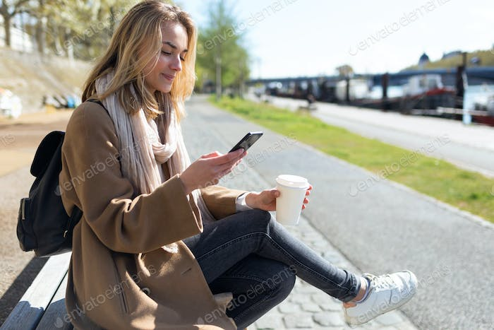 Pretty young woman using her mobile phone while holding cup of c