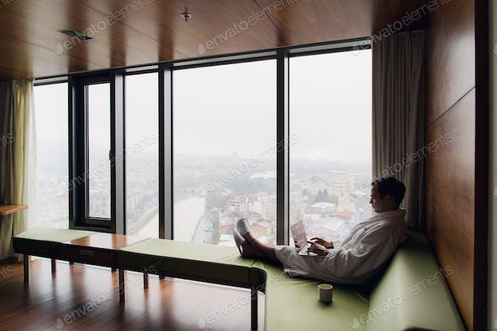 Hombre atractivo disfrutando de su café de la mañana en su Ordenador en su habitación de hotel