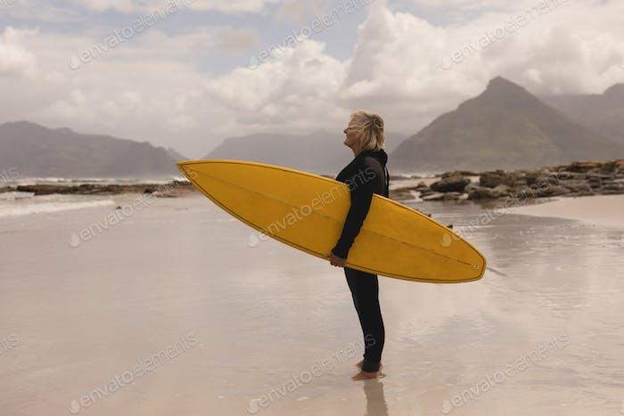 Senior Frau stehend mit Surfbrett am Strand gegen Ebenen im Hintergrund