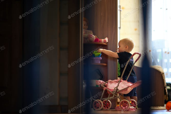 Side view of silhouette baby boy standing by cabinet in dark room