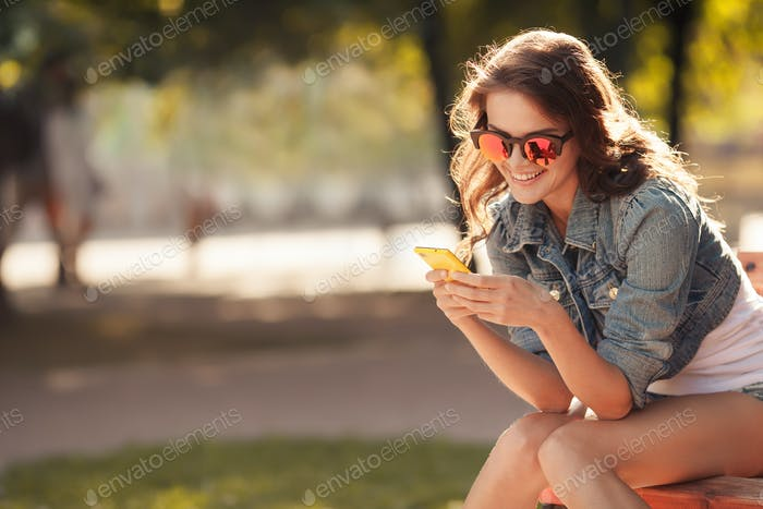 Beautiful Smiling Woman Typing On The Smart Phone In A Park