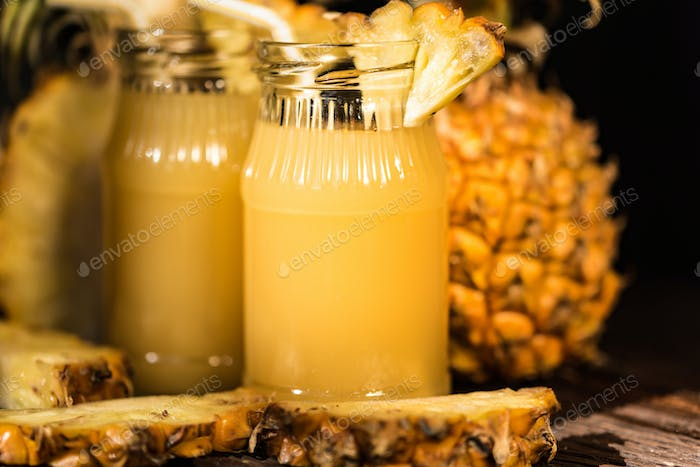 Pineapple juice and slice placed on a wooden table