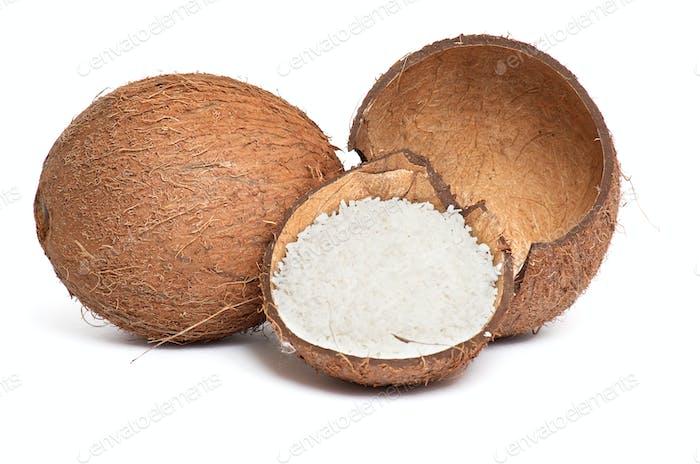 Ganze und gebrochene Kokosnuss auf einem weißen.