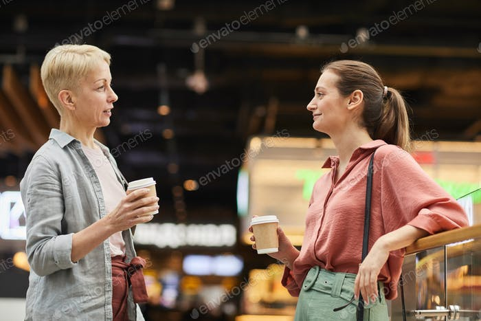 Two women drinking coffee in mall