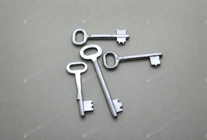Many old vintage keys on a beige background