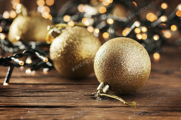 Christmas garland and gold balls on the wooden table