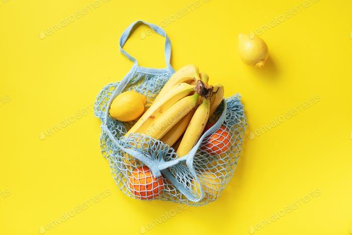 Mesh-Einkaufstasche mit Bio-Banane, Orange, Zitronen auf gelbem Papierhintergrund. Flachlage, Draufsicht