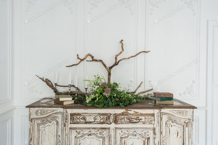 White ancient vintage commode with plants and handmade wool decoration