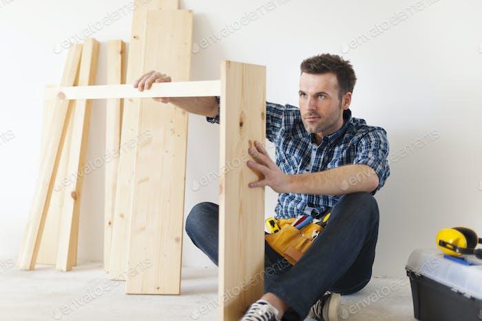 Handsome carpenter working on new furniture