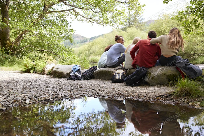 Five young adult friends taking a break sitting on rocks by a stream during a hike, back view