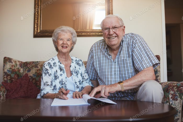 Lächelnd pensionierte Paar Blick über Dokumente