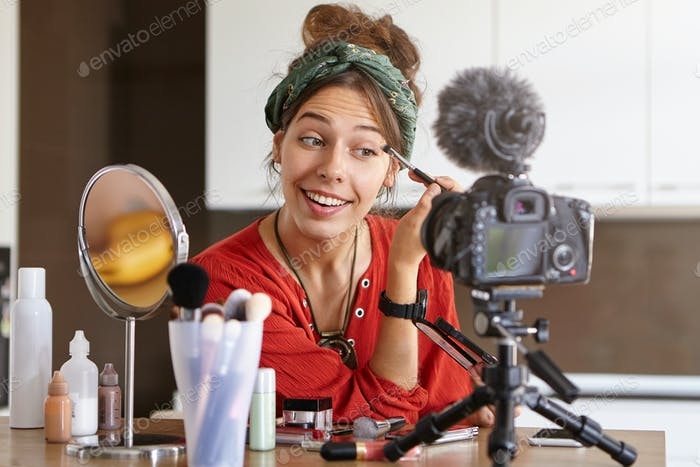 Stylish positive young female beautician or make up artist recording make up video tutorial in livin