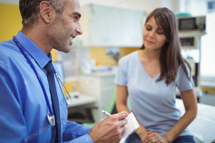 Doctor interacting writing on paper while consulting patient