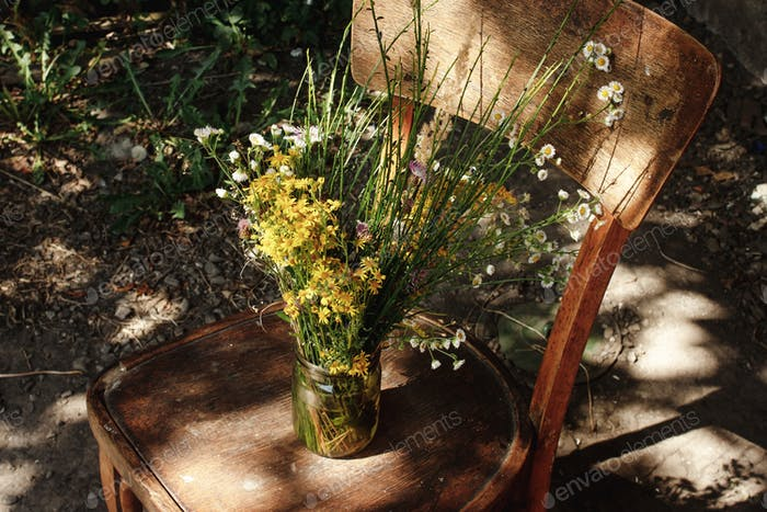 rustic bouquet of wild flowers on old wooden chair in summer days at country house