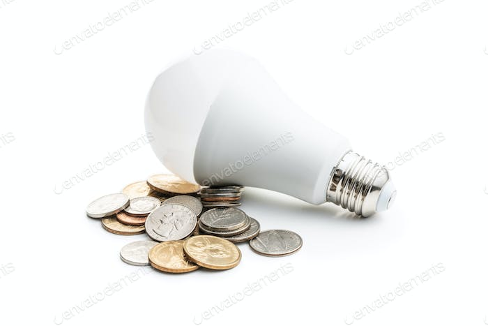 Energy saving light bulb. LED light bulb and dollar coins.