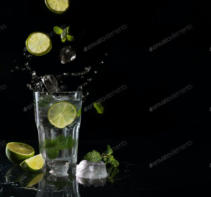 Mojito cocktail on black background with flying ingredients with copy space