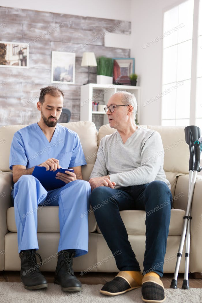 Male doctor with senior man sitting on couch in nursing home writing notes on clipboard