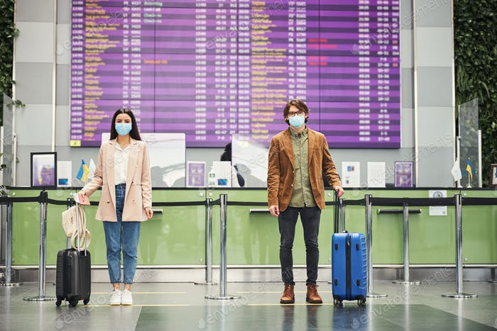 Joven y mujer manteniendo la distancia social segura en el aeropuerto