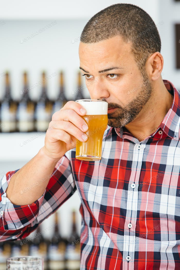 Bearded man smelling light beer