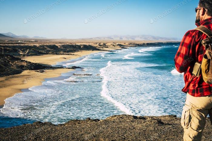 Hombre de pie con mochila y hermosa playa