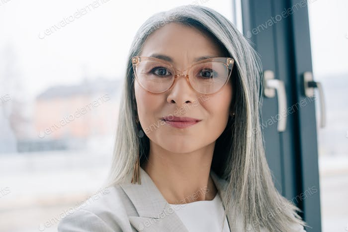 attractive confident asian businesswoman with grey hair in grey suit and eyeglasses looking at