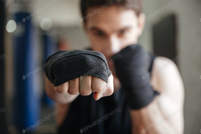Close up  view of young boxer doing exercise in gym
