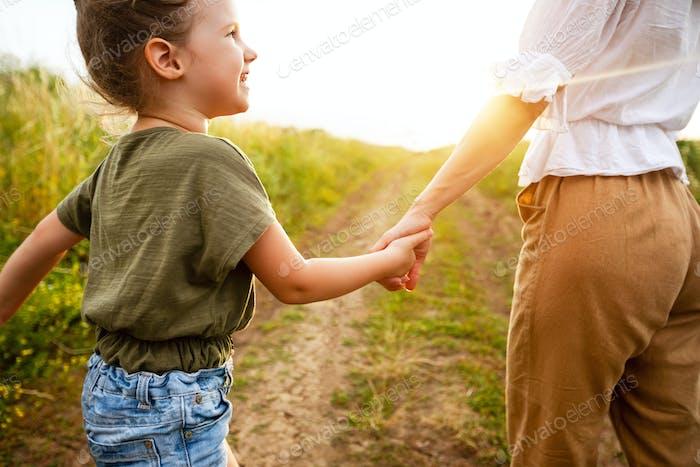 Mama nimmt ihre kleine Tochter sanft an der Hand