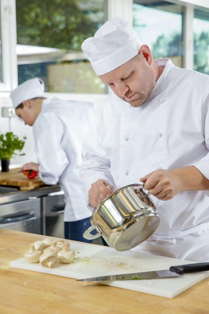 Professional chefs makes food dishes in large kitchen