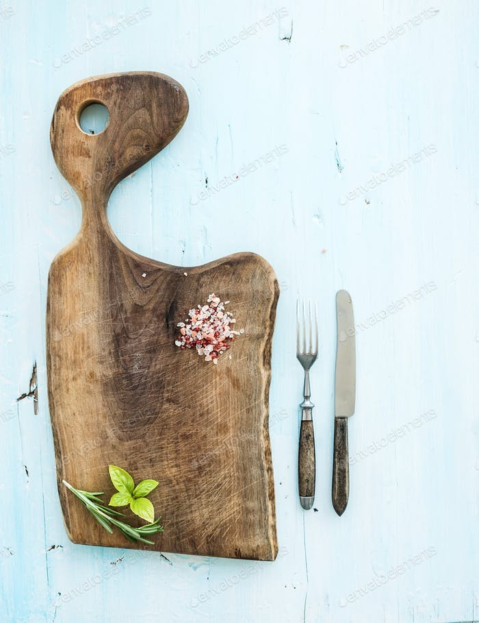 Kitchen-ware set. Walnut wooden chopping board, knife, fork, spices and herbs