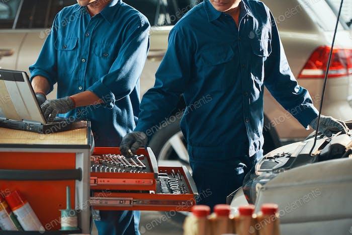 Car mechanic choosing wrench