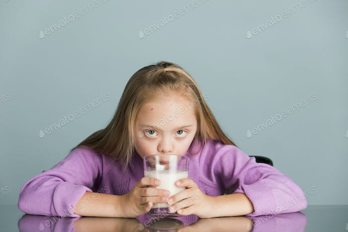 Cute girl with down syndrome drinking milk