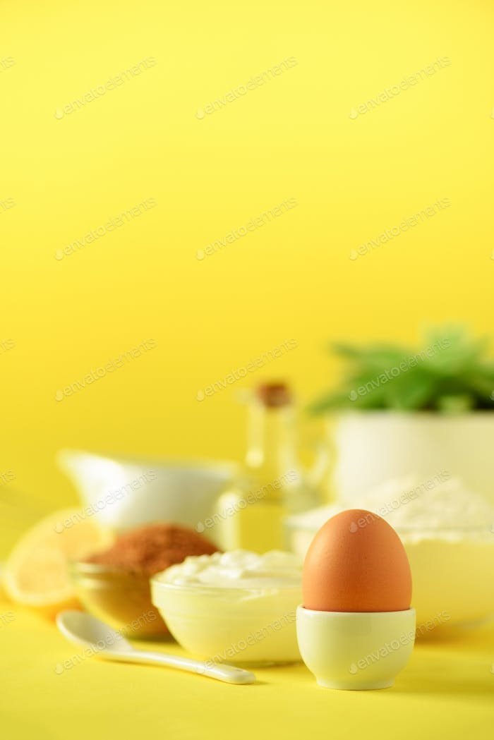 White cooking utensils on yellow background. Food ingredients. Macro of egg. Cooking cakes and