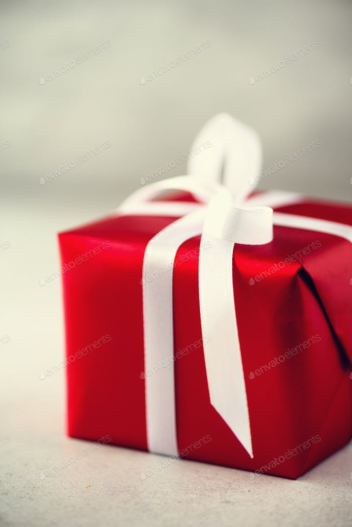 Rote Geschenkbox auf grauem Betonuntergrund, Kopierraum. Weihnachten, Neujahr, Geburtstagsparty, Valentinstag