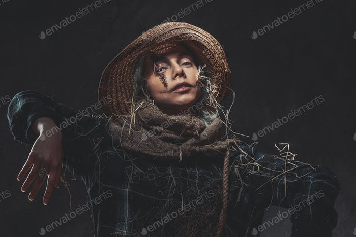 Awful scarecrow posing in dark background with hat