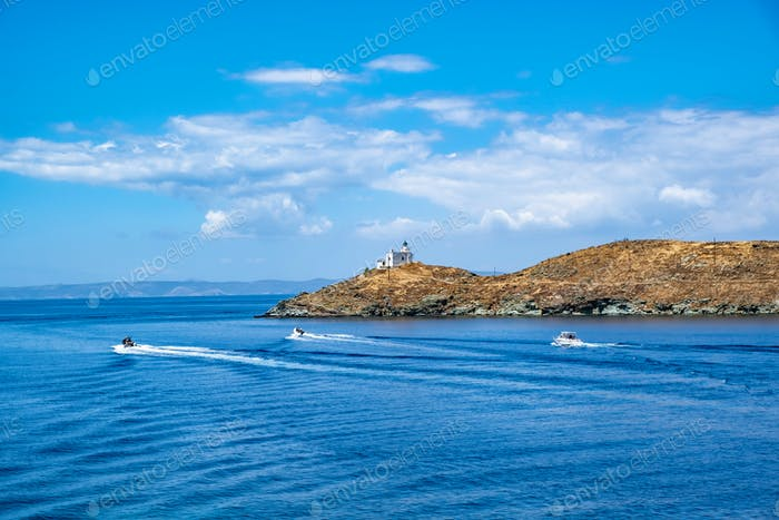 Inflatable speed boats cruising in mediterranean sea.  Lighthouse on a cape.