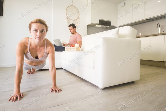 Caucasian young people couple do fitness at home
