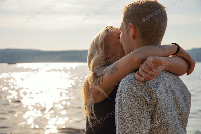 Kissing couple in romantic embrace on beach at summer