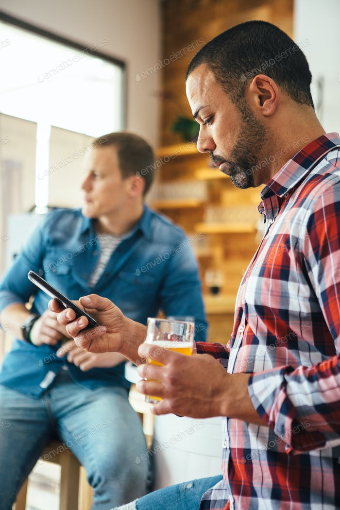 Man using phone while holding beer