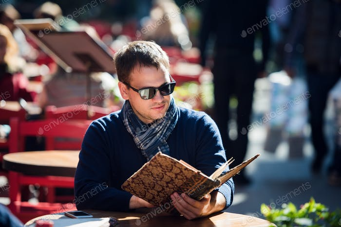 Young handsome man looking at the menu outdoors