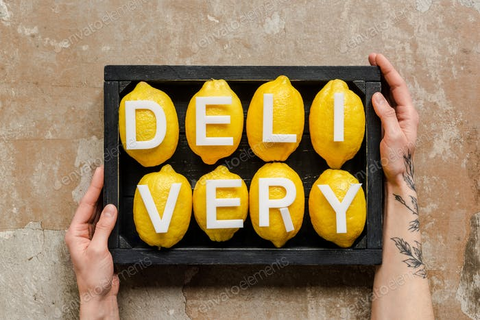 Partial View of Woman Holding Wooden Box With Word Delivery on Lemons on Weathered Surface