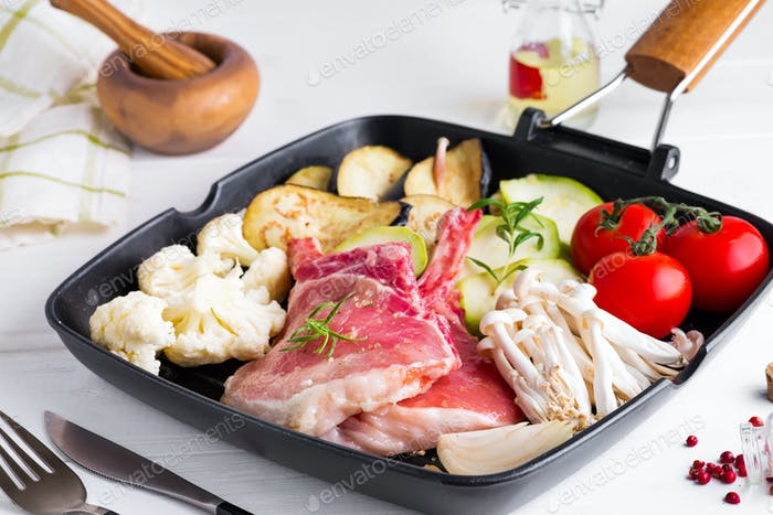 Raw lamb ribs marinating with fresh vegetables in a grill pan on a white stone background