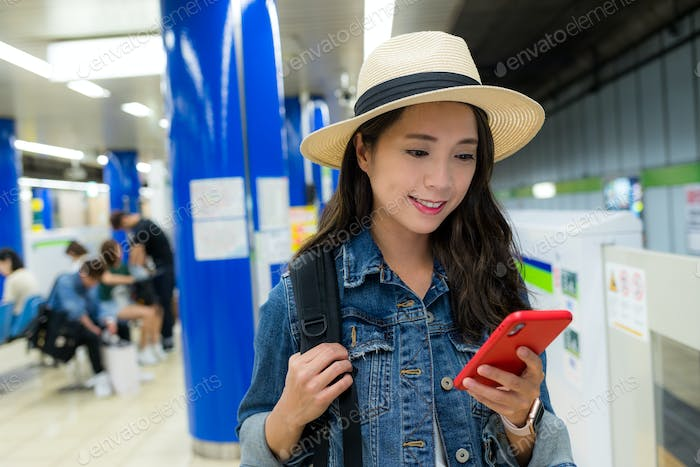 Woman use of smart phone in station