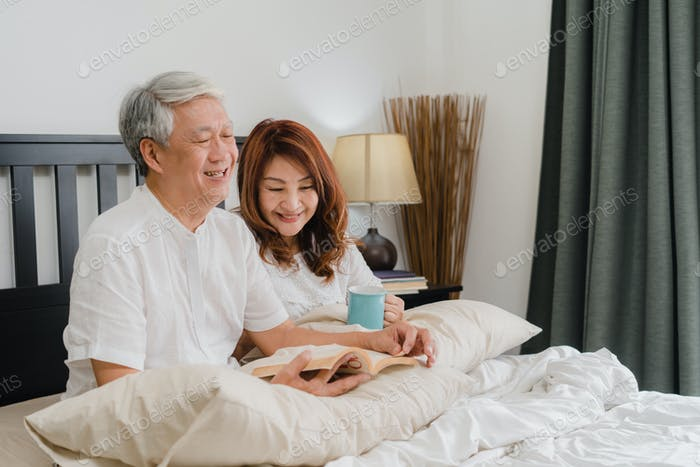 Asian senior couple talking on bed at home. Husband and wife happy drink coffee and read book