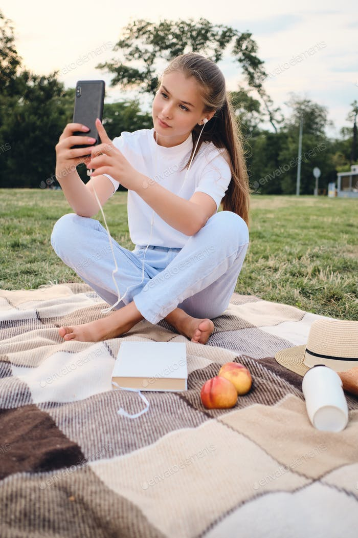 Beautiful teenage girl in earphones dreamily taking photo on cellphone on picnic in city park