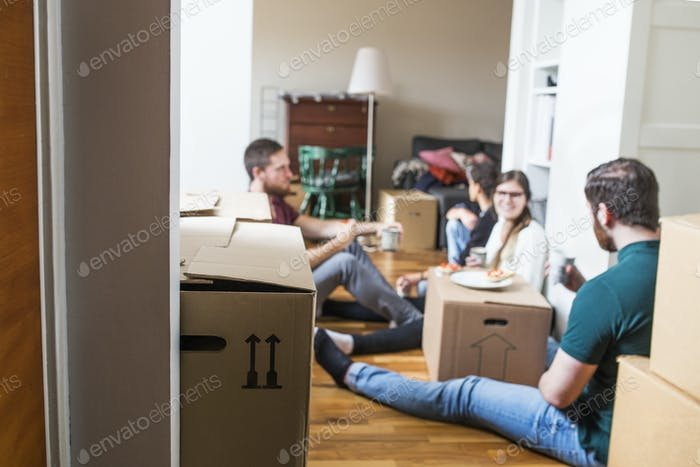 Group of friends eating sandwiches while moving house